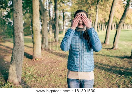 Front view portrait of beautiful young woman covering eyes with hands and standing in autumn park