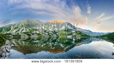 Panorama of the mountain lake with coasts overgrown with grass and mountain pine and the craggy of the mountain gorge reflected in water on the sunset
