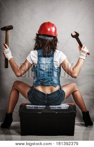 Sex equality and feminism. Back of sexy girl sitting on toolbox and holding wrench spanner and hammer tools on gray. Young attractive woman working as construction worker. Studio shot.
