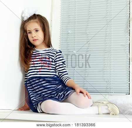 Little girl in blue striped dress and a white bow on her head.She sits at the window with sad eyes.