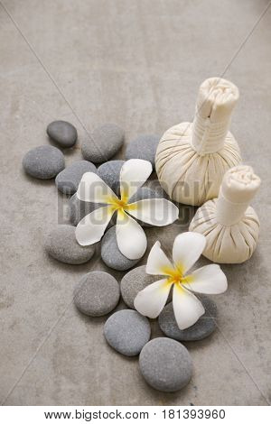 Two frangipani with gray stones with herbal ball on grey background.