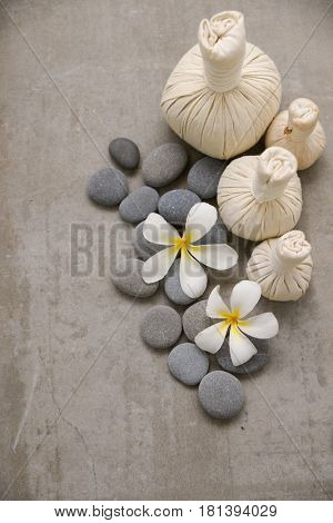 Two frangipani with gray stones with three herbal ball on grey background.