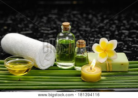 spa concept –frangipani and towel,candle ,soap, oil on green long leaf
