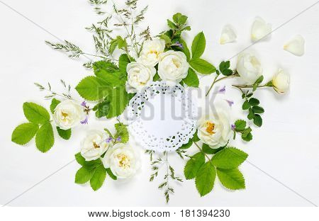Decorative composition in retro style consisting of round white paper openwork doily and white wild rose flowers with green leaves on white background. Top view flat lay