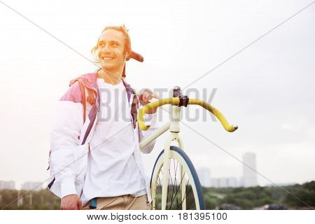 Smiling Man In Blank T-shirt With Bicycle In Green Field (intentional Sun Glare And Bright Color)