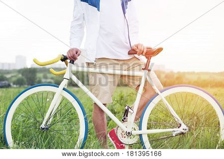 Young Man Standing With Bicycle In Green Field Outdoors (intentional Sun Glare And Bright Colors)
