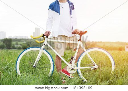 Young Man Standing With Bicycle In Green Field (intentional Sun Glare And Bright Colors)