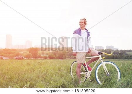Young And Handsome Man In Blank T-shirt Sitting On His Bicycle In The Field (intentional Sun Glare A