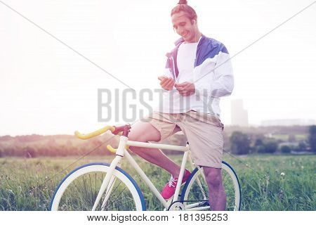 Young And Handsome Man With Bicycle In Green Field Looking At Smartphone (intentional Sun Glare And