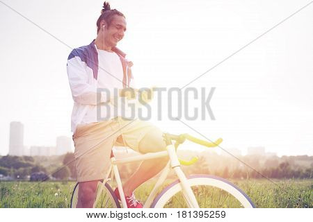 Young Long Hair Man With Bicycle In Green Field Looking At Smartphone (intentional Sun Glare And Vin