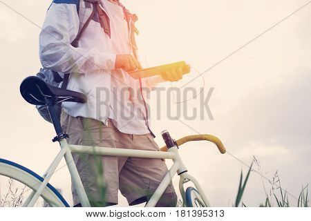 Young Man With Bicycle In The Green Field With Tablet Computer At Sunset (intentional Sun Glare And
