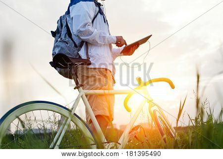 Young Man With Bicycle In The Green Field Touching Tablet Computer (intentional Sun Glare And Dark C