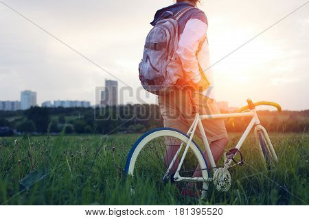 Young Man With Bicycle In The Green Field Looking At Sunset (intentional Sun Glare And Dark Colors)