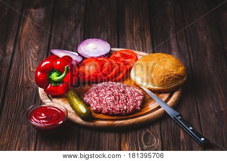 Raw Ground beef meat Burger steak cutlets with seasoning, cheese, tomatoes, salad and bun on vintage wooden boards