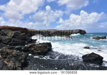 Waves crashing ashore on Aruba's black sand stone beach.