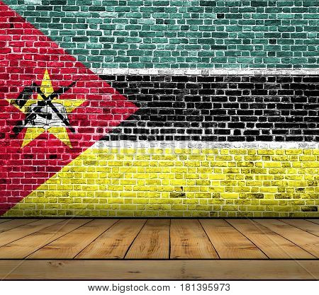 Mozambique flag painted on brick wall with wooden floor