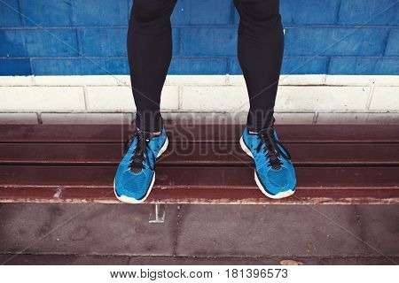 Close-up Of Athlete's Legs With Running Shoes Standing On Bench