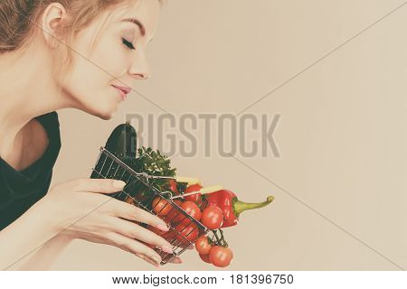 Woman Holds Shopping Basket With Vegetables, Smelling