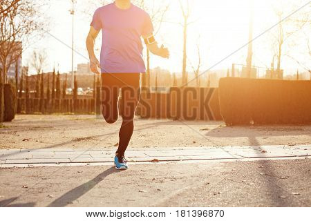 Silhouette Of Running Athlete In The Park  At Sunset (with Little Motion Blur And Intentional Sun Gl