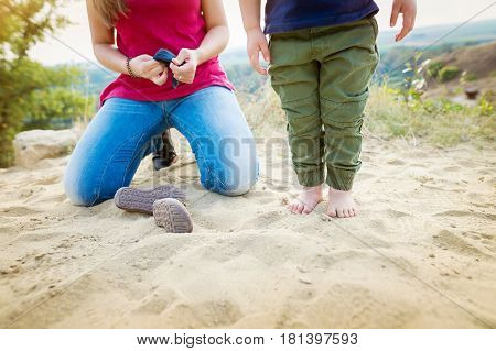 Unrecognizable mother with son on sand beach at the lake, taking his shoes off. Sunny spring day.