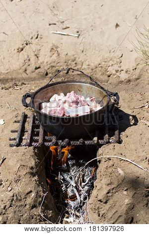 meat in a cauldron on fire . A photo