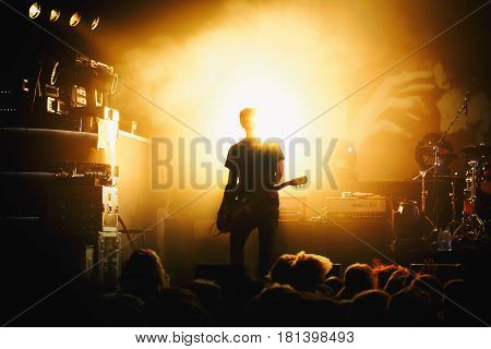 Silhouette Of Guitar Player In Action On Stage
