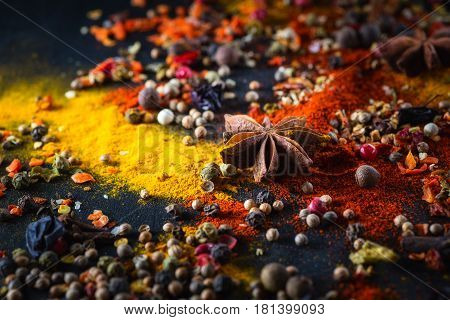Different varicolored seasonings (coriander a mixture of peppers peas turmeric sweet red pepper powder anise) on a black background chalkboard
