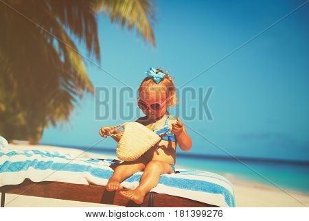 little girl with sunblock cream at beach, sun protection