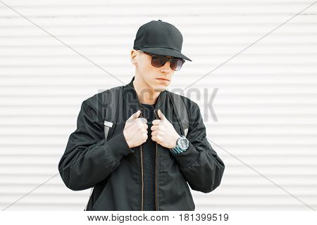 Handsome American Young Man In A Black Baseball Cap And Black Sunglasses And A Fashionable Jacket Ne