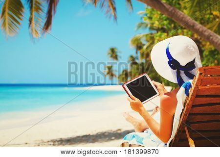 woman with touch pad on tropical beach, vacation concept