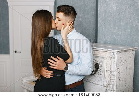 Beautiful Young Elegant Couple Kissing Near A White Vintage Piano
