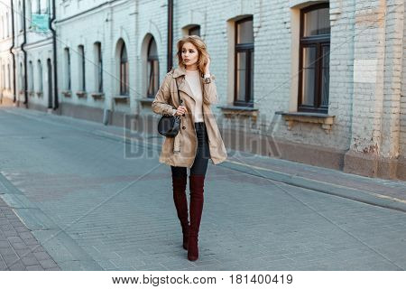 Stylish Young Girl In A Trendy Coat And Fashionable Boots With Black Bag Walking In The Old Town