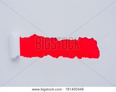 Tearing a white paper frame hole on red background