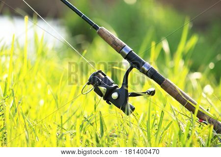 Fisherman's fishing rod with inertia-free coil in summer on shore of lake