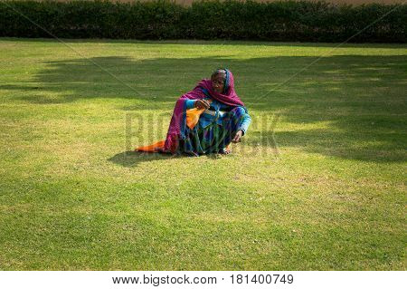 Female Indian Mow Hand Lawn With Green Grass. Hard Work Of Poor People In India.