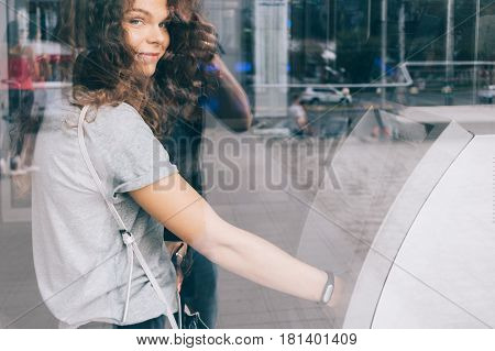 Young curly-haired smiling woman withdraws money from an ATM in the city the reflection of the street on the glass