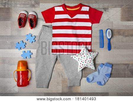 Baby clothes and accessories on wooden background