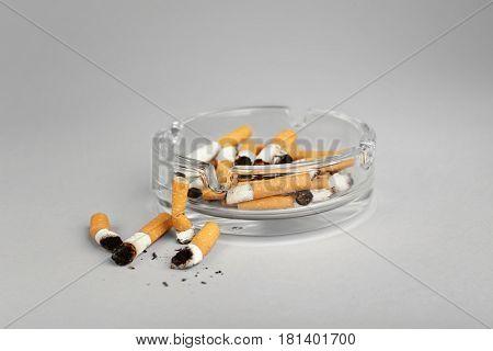 Cigarette butts in ashtray on light background