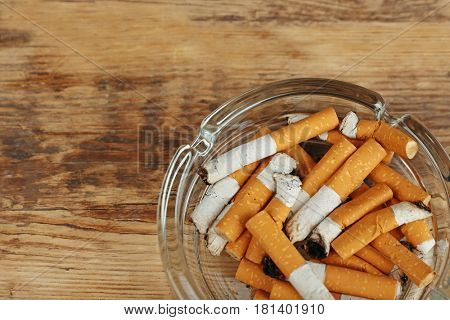 Cigarette butts in ashtray on wooden background
