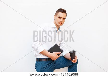 Handsome Stylish Man With Coffee And A Notepad In A White Stylish Shirt Near A Blank White Wall