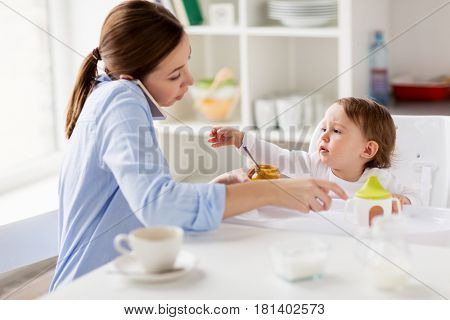 family, food, eating, multitasking and people concept - mother with puree and spoon feeding little baby sitting in highchair and calling on smartphone at home