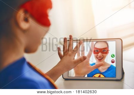 Mother and her child playing together. Girl and mom in Superhero costumes. Mum and kid talking by using video link, having fun and smiling. Family holiday and togetherness.