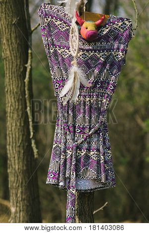 On the tree hanging dreamer a woman's dress. Indie style