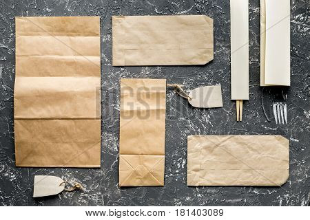 food delivery service workdesk with paper bags and flatware on gray background top view mockup