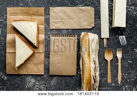 food delivery service workdesk with paper bags and sandwich on gray background top view mock-up