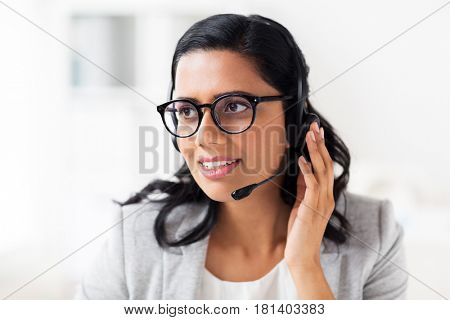 communication, business, people and technology concept - smiling businesswoman or helpline operator with headset talking at office