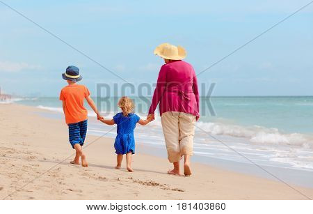 grandmother with grandkids- little boy and girl- walk at tropical beach