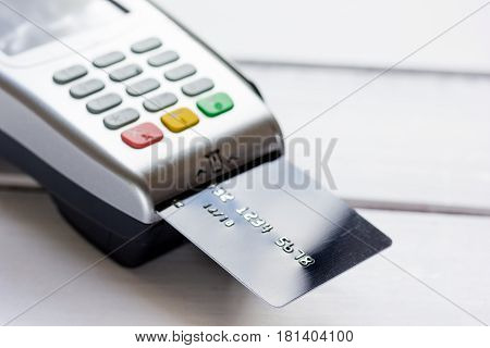 payment terminal with credit card on white wooden table background