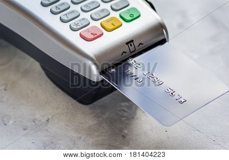 payment terminal with credit card on stone table background