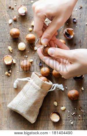 Hands Opening Macadamia Nut With Opener. Healthy Food